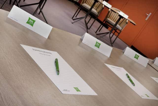 Gros plan sur une table de la Salle Fil Good (stylos et papier mis à disposition des participants par l'hotel Ibis Styles)